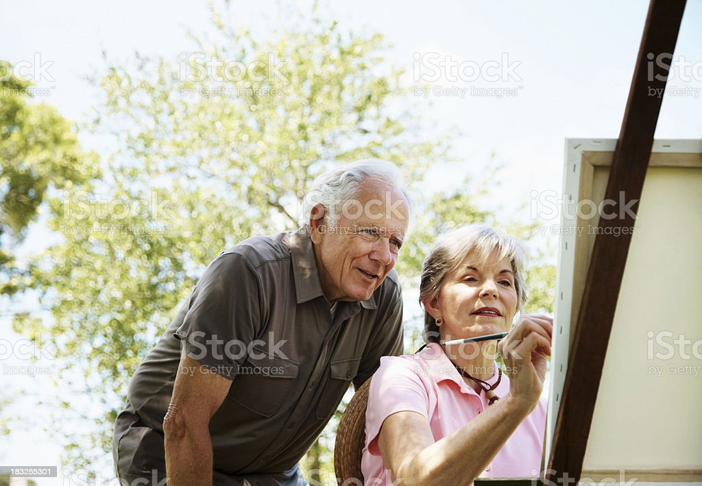 Mature female painting on canvas with her husband stock photo