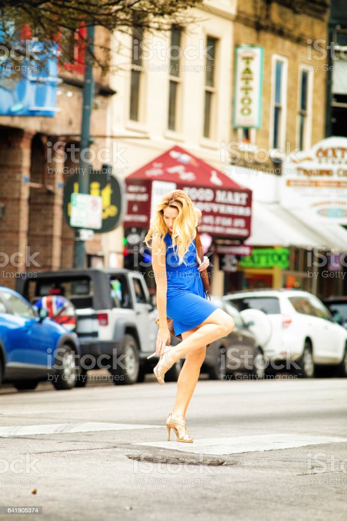 Mature female readjusts her shoe while crossing the street stock photo