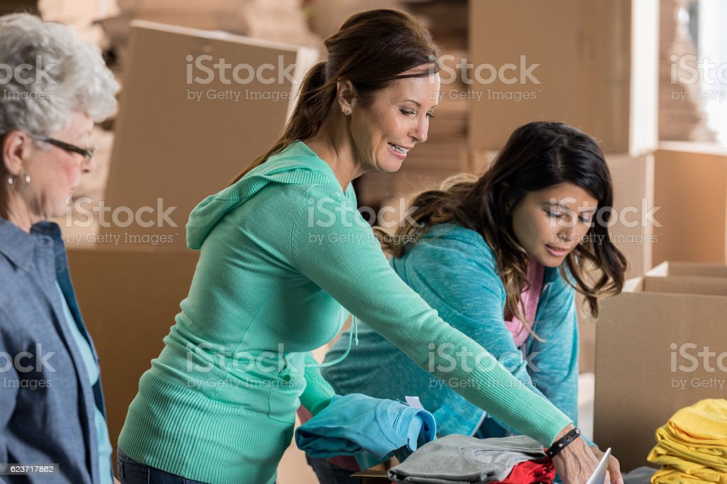 Mature female small business owner fills online order in warehouse stock photo