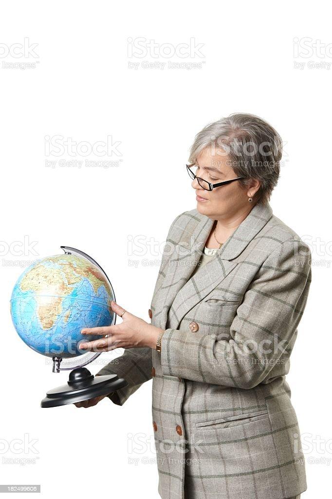 Mature female teacher explaining on globe royalty-free stock photo