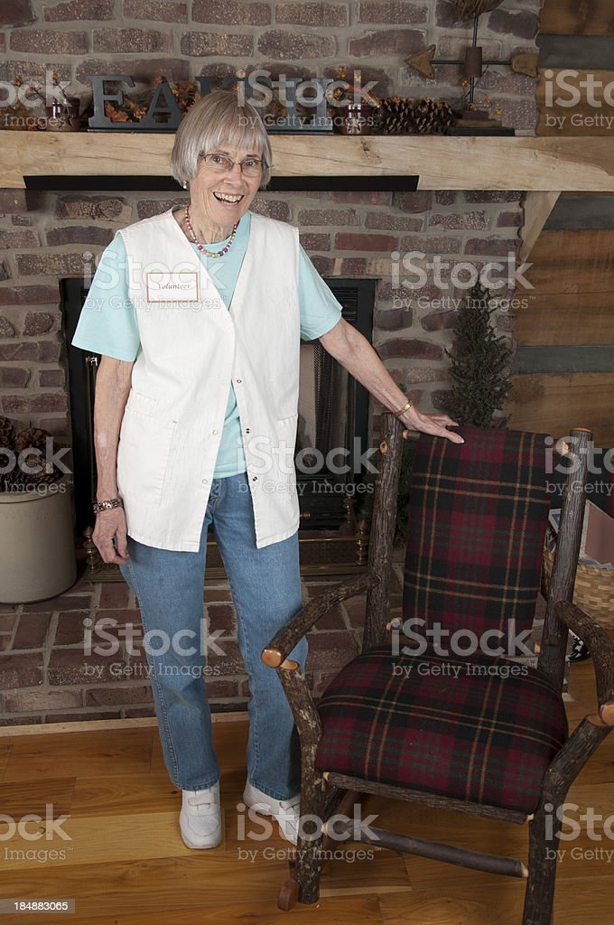 Mature Female Volunteer Stands by Rustic Chair royalty-free stock photo