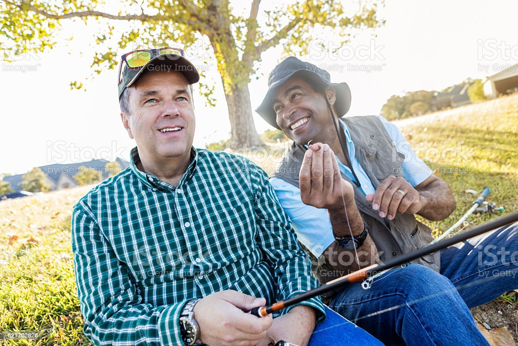 Mature fisherman baits hook while fishing with his friend stock photo