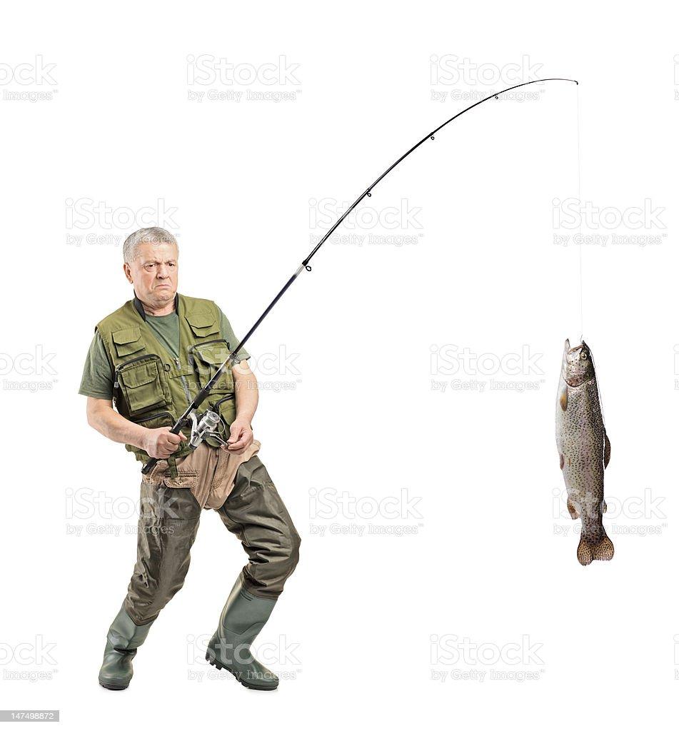 Mature fisherman catching a fish stock photo