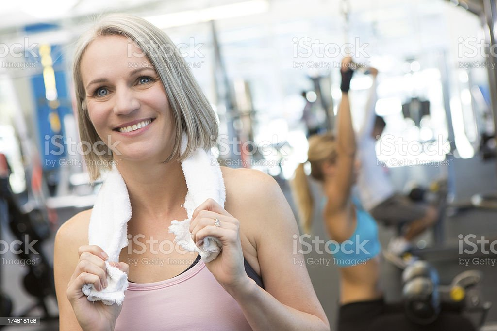Mature fit woman taking break from gym workout royalty-free stock photo