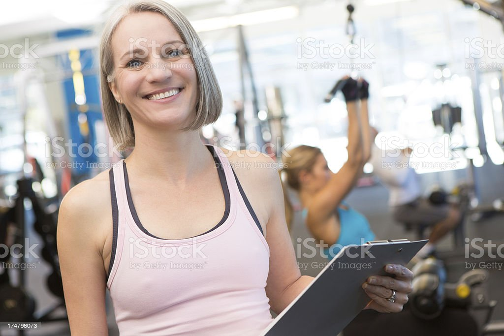 Mature fitness instructor in busy gym royalty-free stock photo