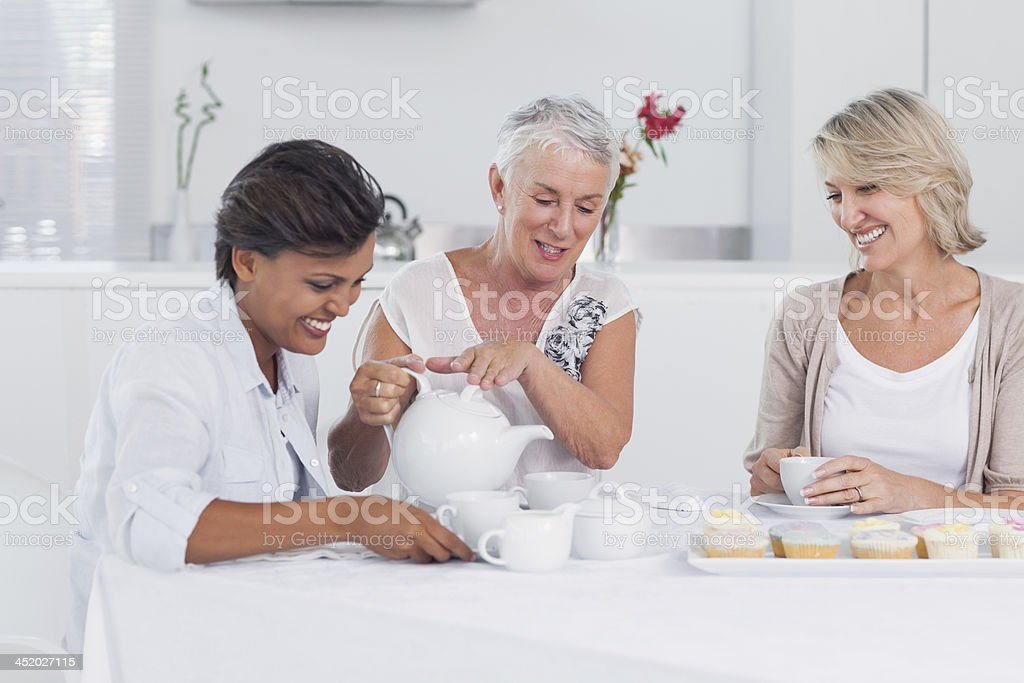 Mature friends enjoying afternoon tea together royalty-free stock photo
