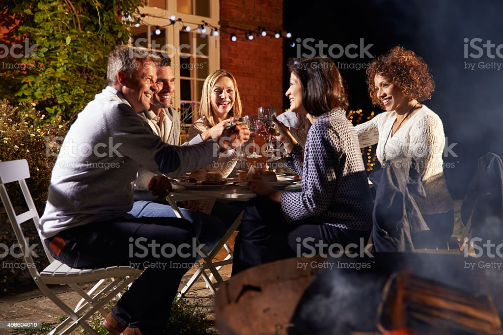 Mature Friends Enjoying Outdoor Evening Meal Around Firepit stock photo