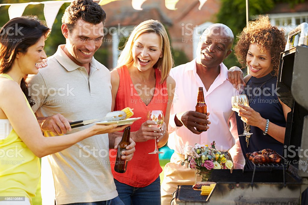Mature Friends Enjoying Outdoor Summer Barbeque In Garden stock photo