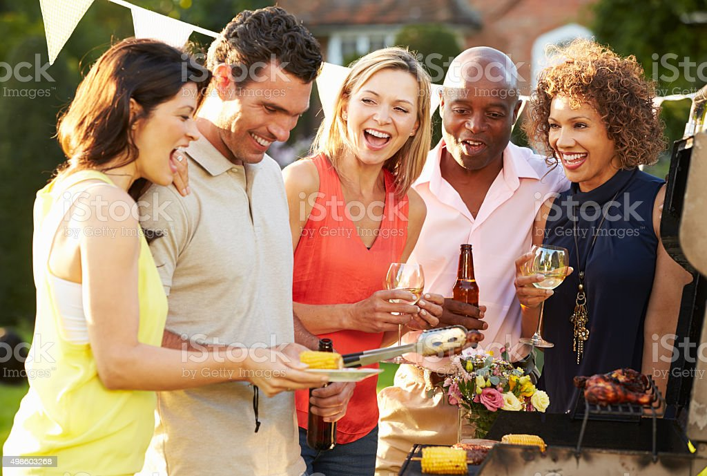 Mature Friends Enjoying Outdoor Summer Barbeque In Garden stock photo