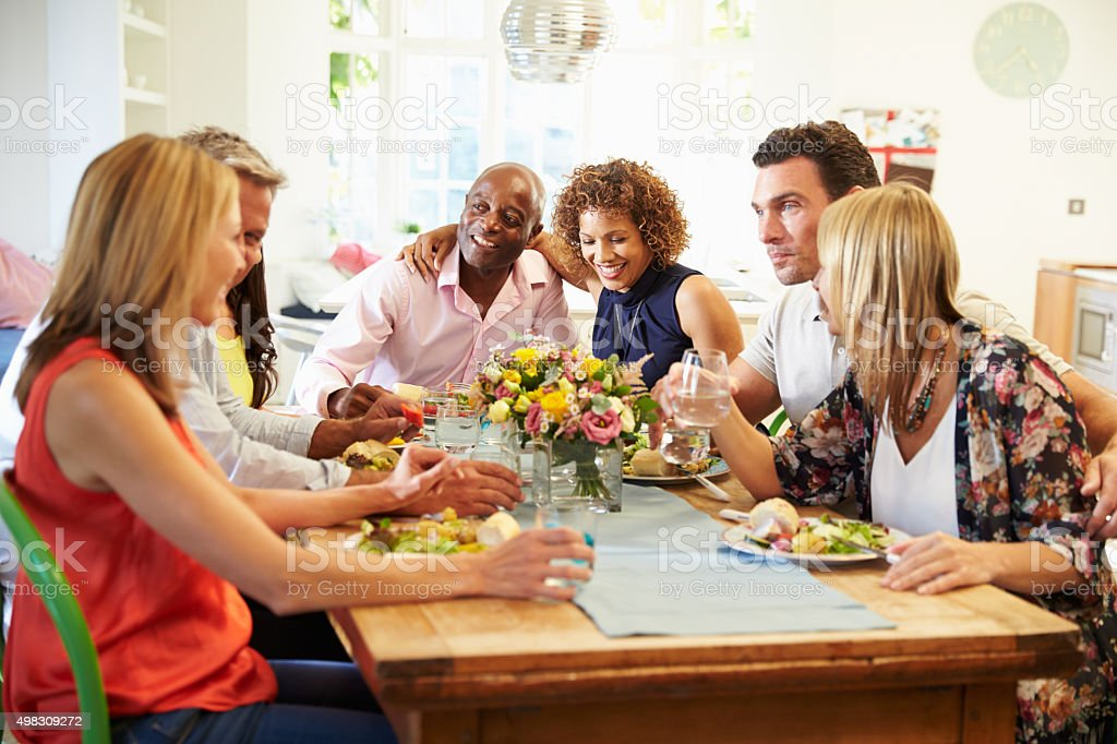 Mature Friends Sitting Around Table At Dinner Party stock photo