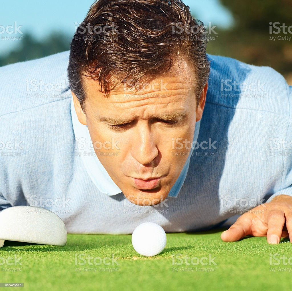 Mature golfer blowing at the ball stock photo