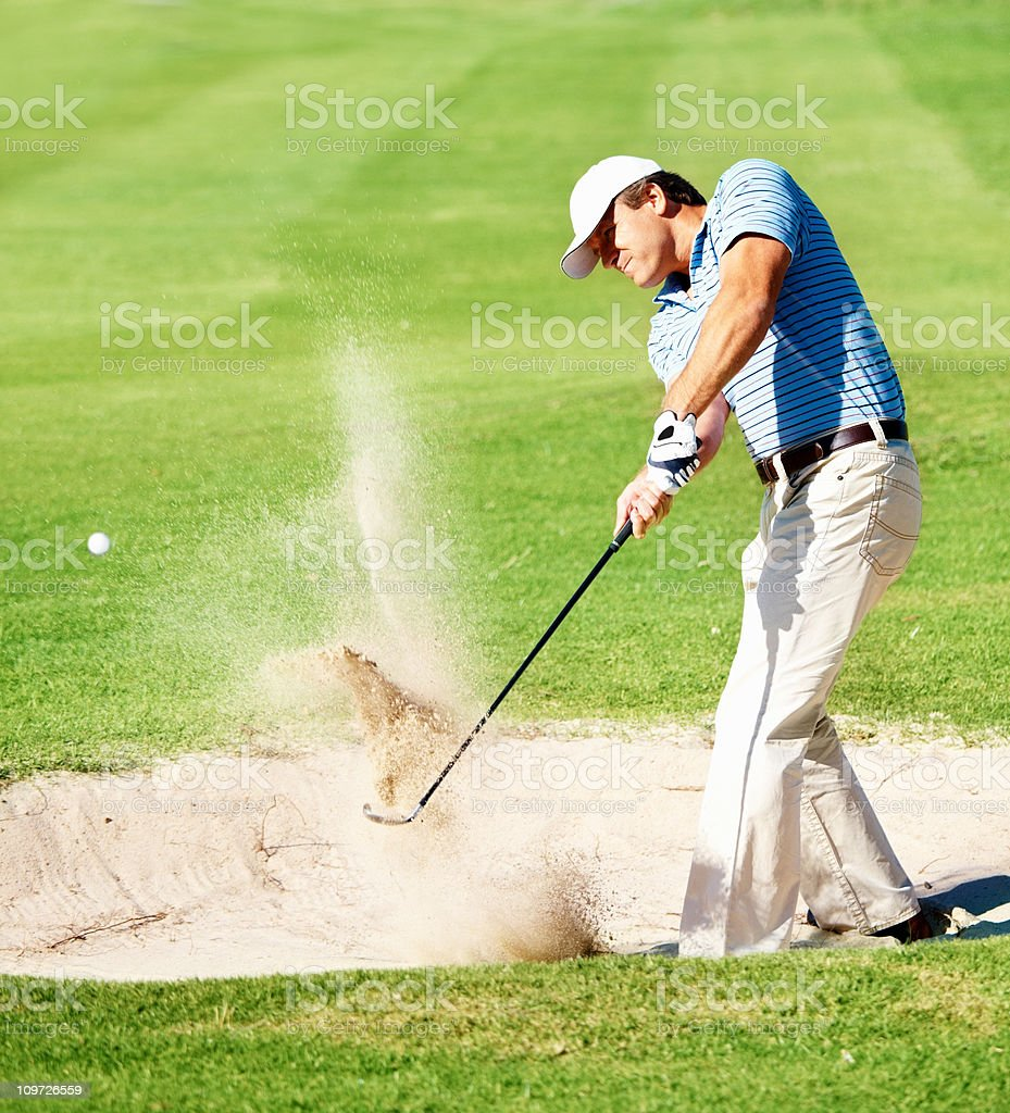 Mature golfer chipping the ball from sand trap stock photo
