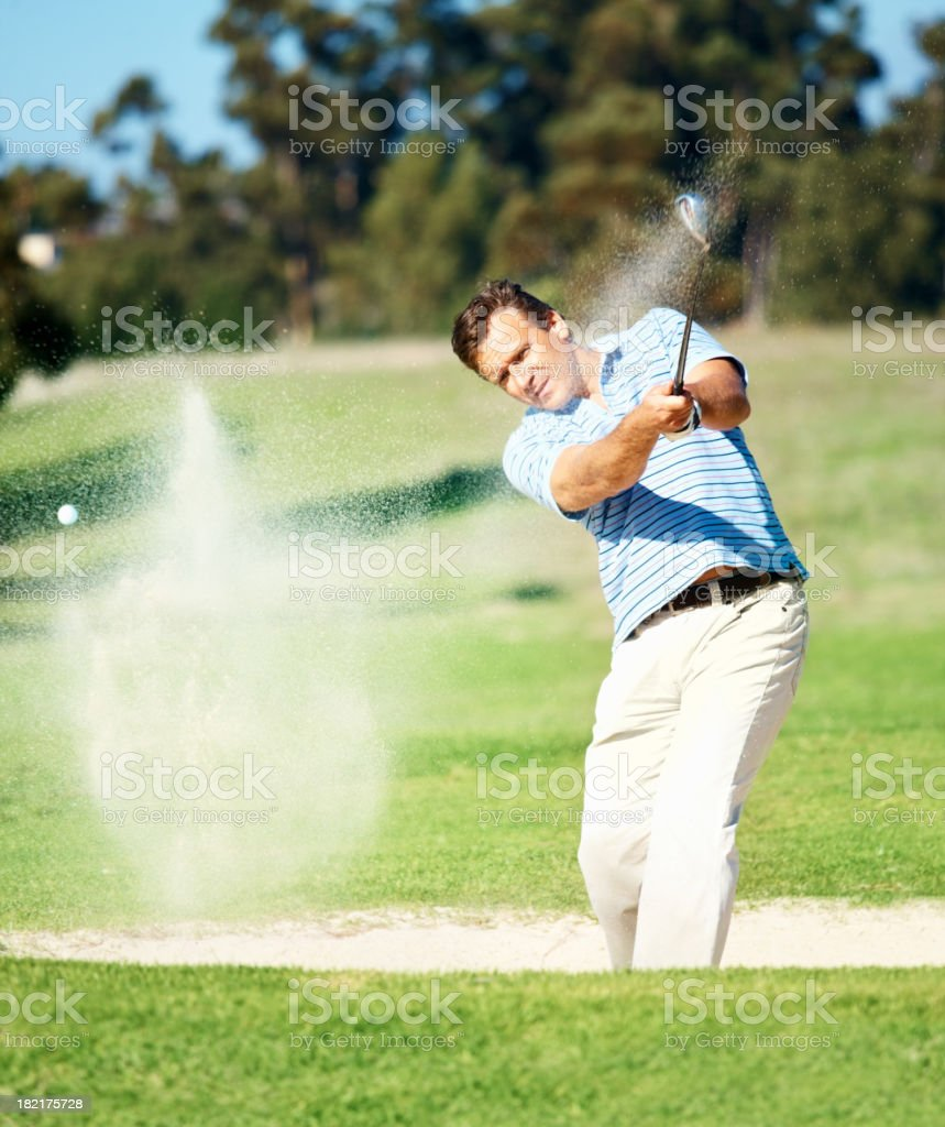 Mature golfer hitting out of a sand trap stock photo