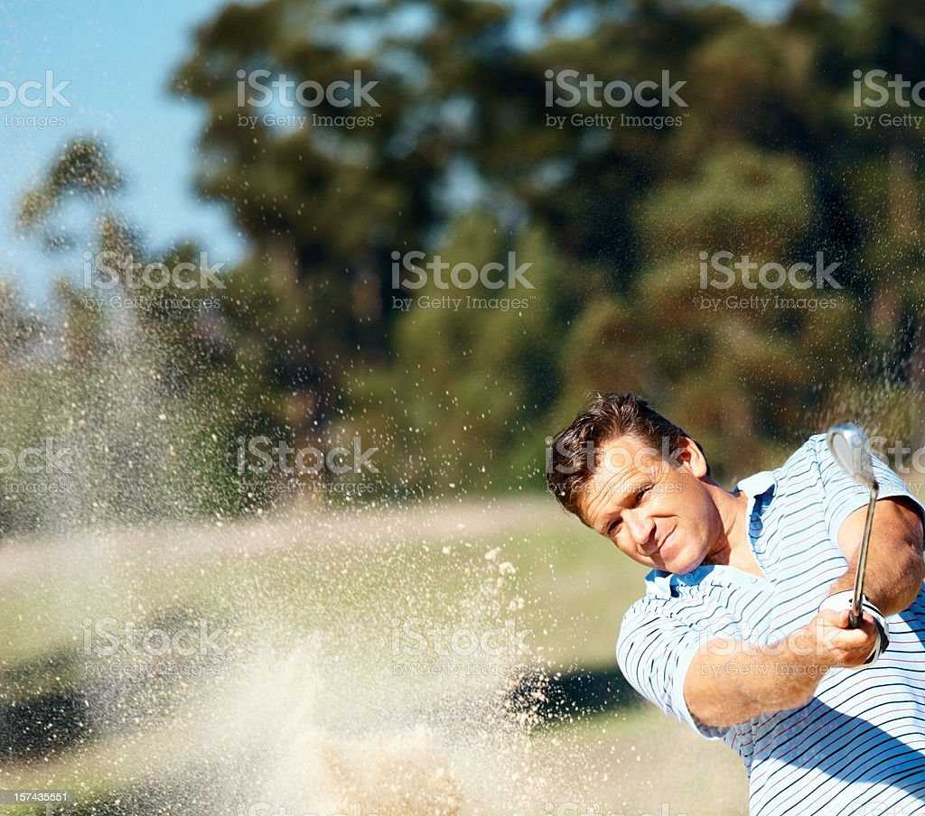 Mature golfer playing out of a sand bunker royalty-free stock photo