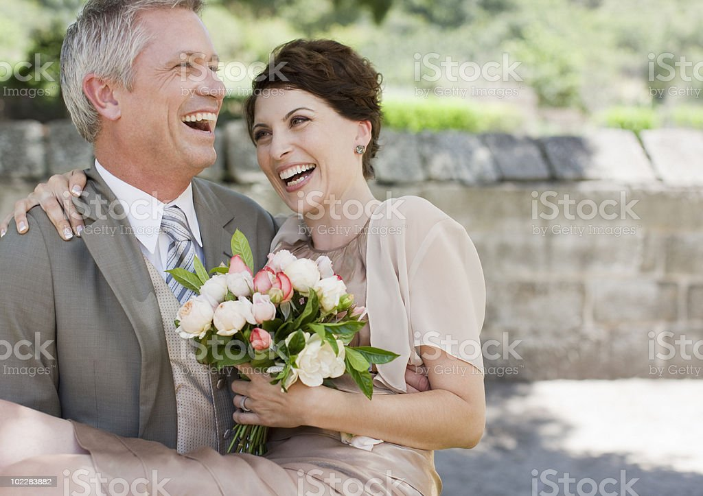 Mature groom carrying bride stock photo