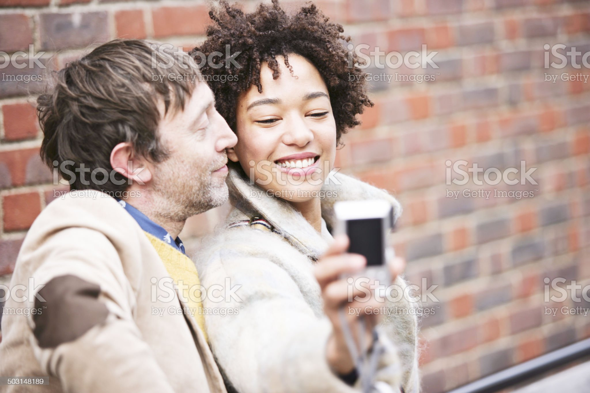 Mature guy and beautiful woman making selfportrait royalty-free stock photo