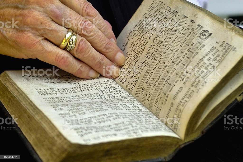 Mature hand with old book royalty-free stock photo
