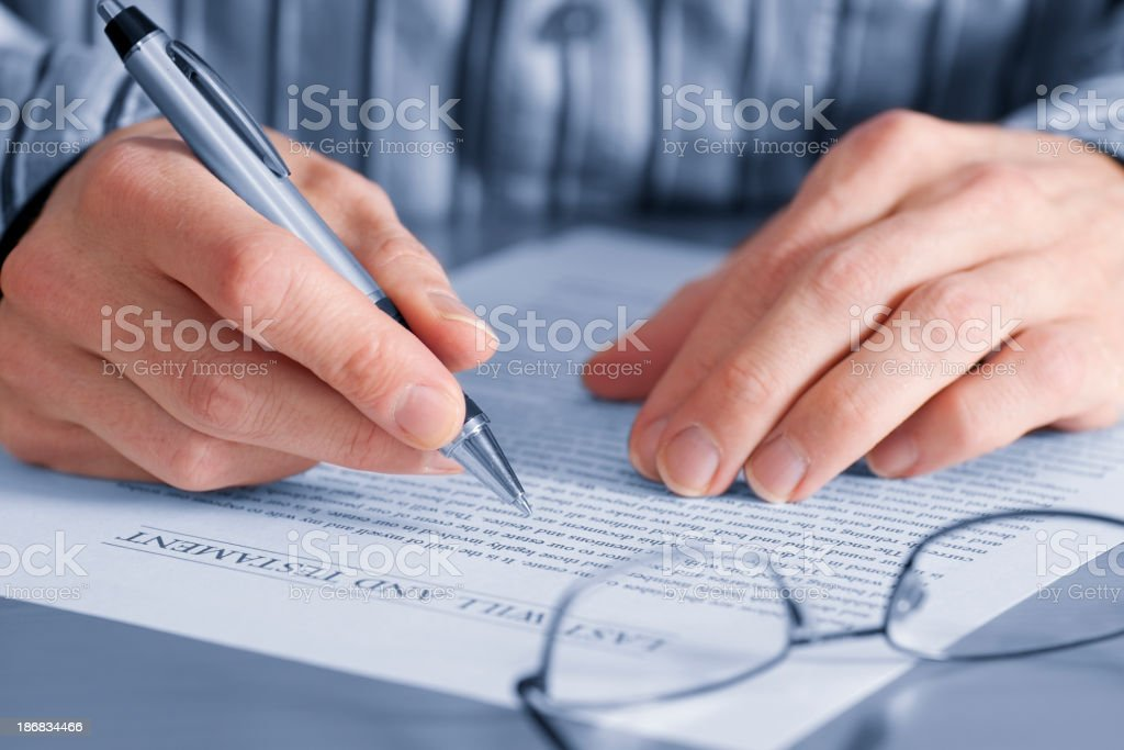 Mature hands filling out last will and testament royalty-free stock photo