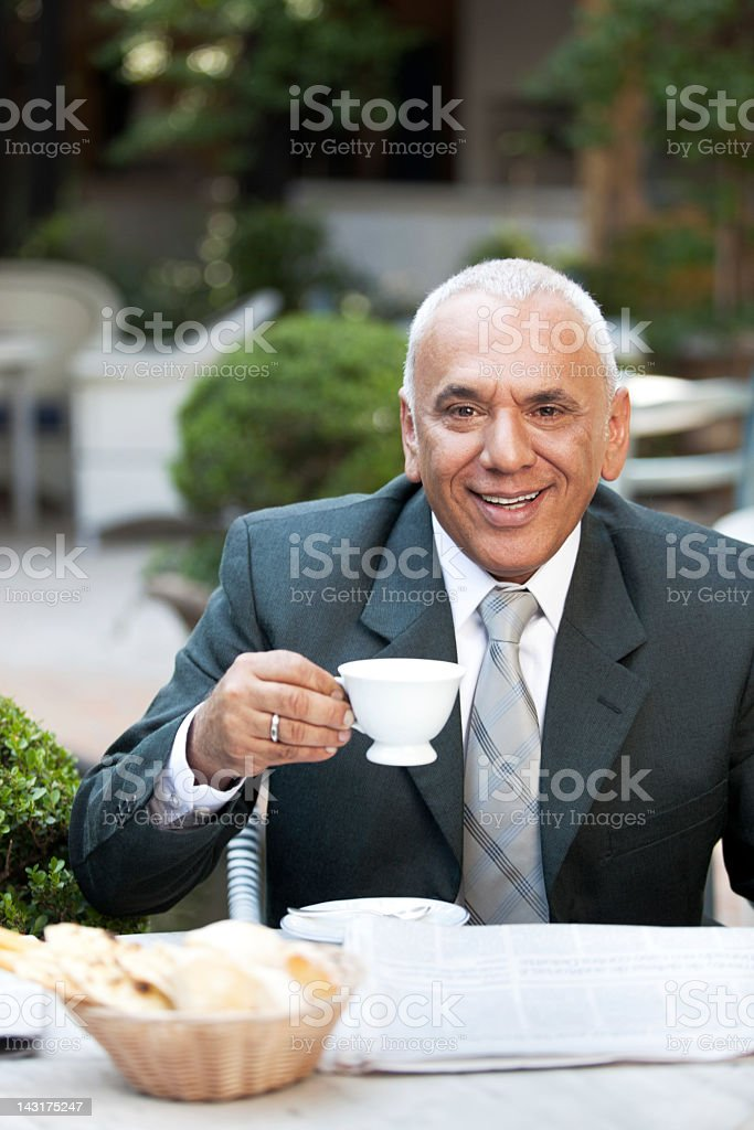 Mature happy businessman enjoying his morning breakfast and fresh newspaper. royalty-free stock photo