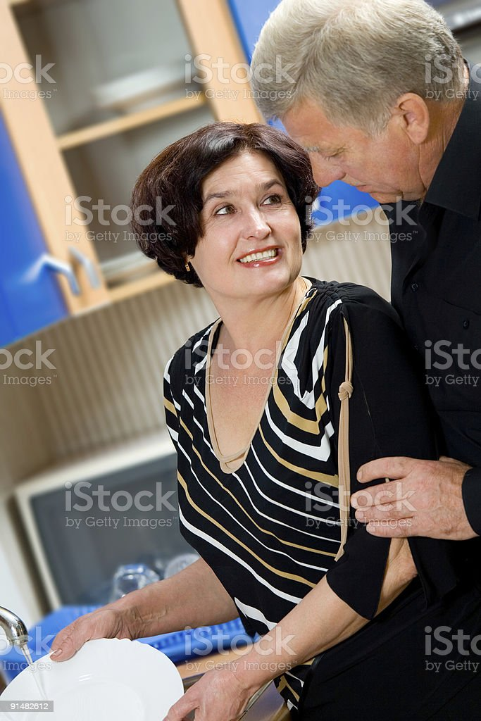 Mature happy couple at kitchen, focus on woman royalty-free stock photo