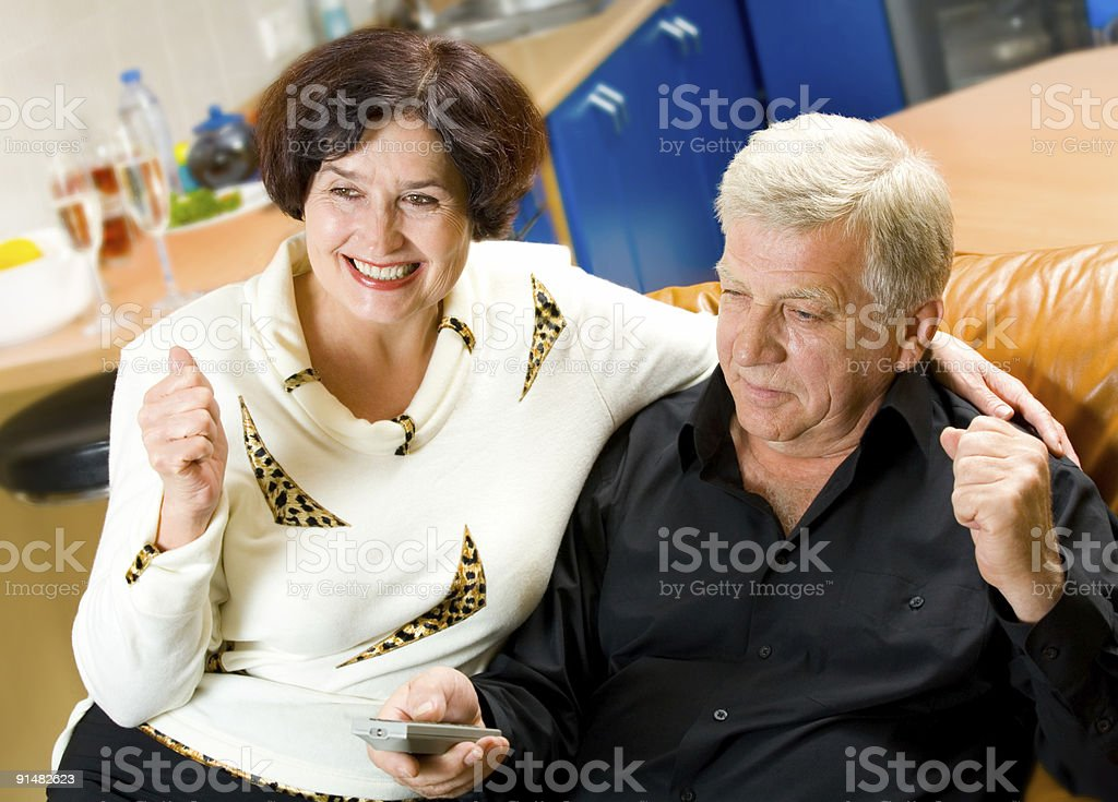 Mature happy smiling couple watching TV together at home royalty-free stock photo