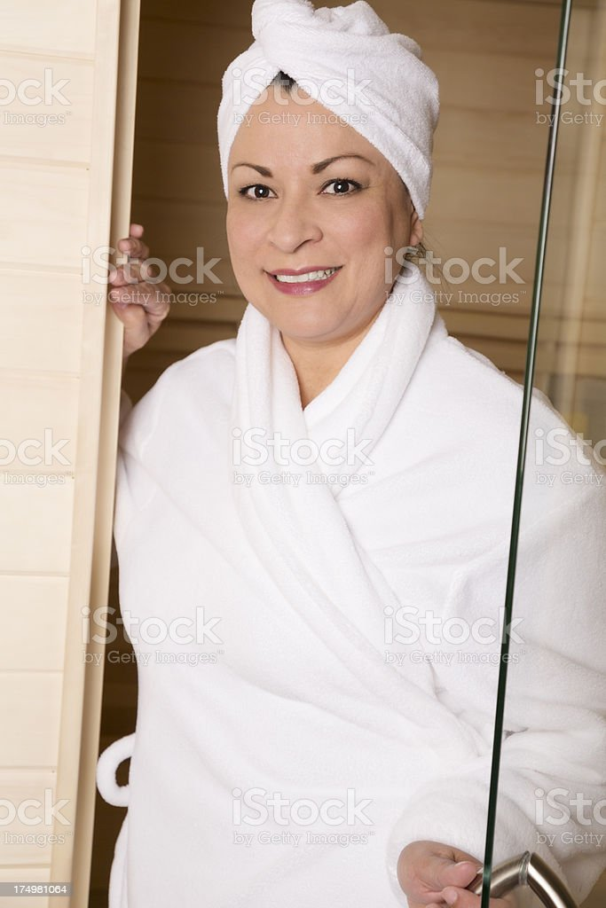 Mature happy woman exiting infrared sauna royalty-free stock photo