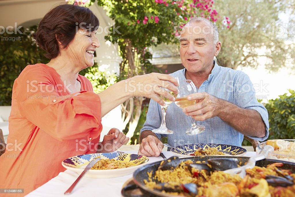 Mature Hispanic Couple Enjoying Outdoor Meal At Home stock photo