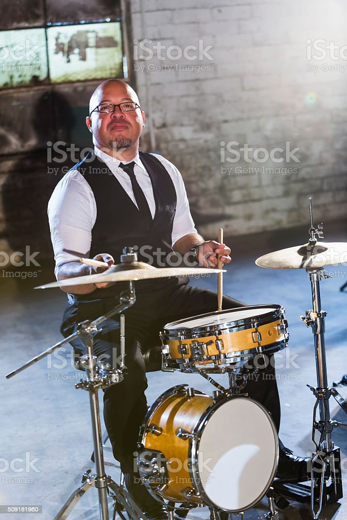 Mature Hispanic man playing the drums stock photo