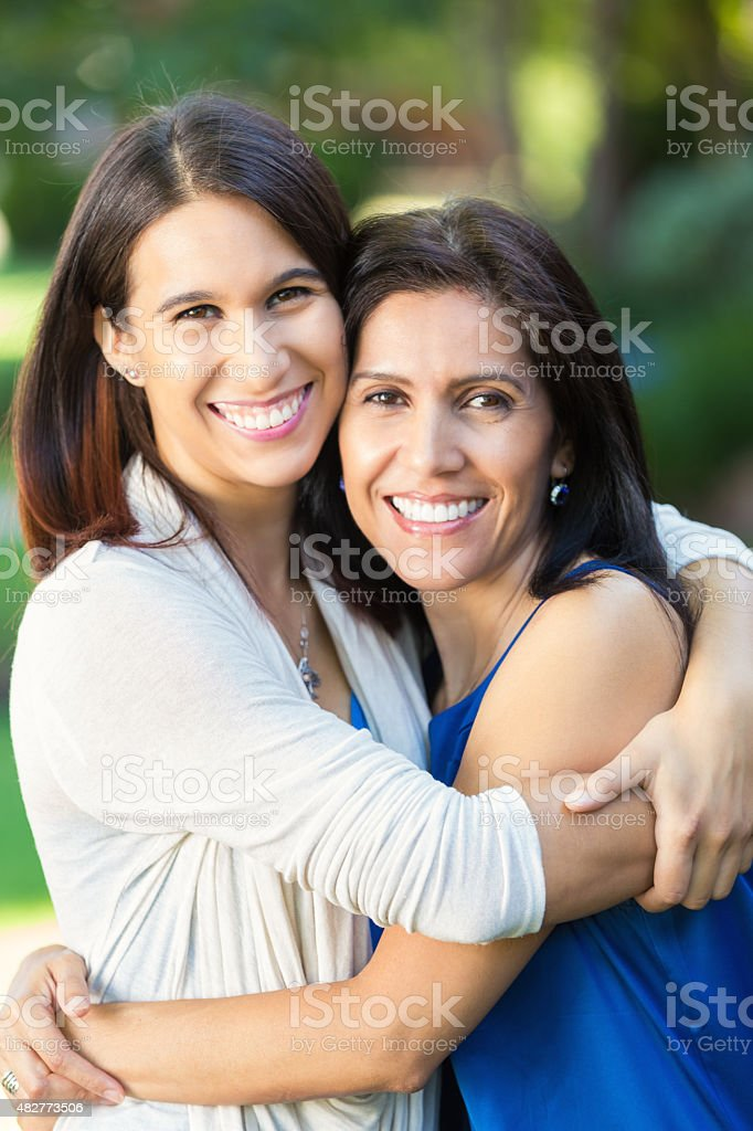 Mature Hispanic woman is smiling while hugging young adult daughter stock photo