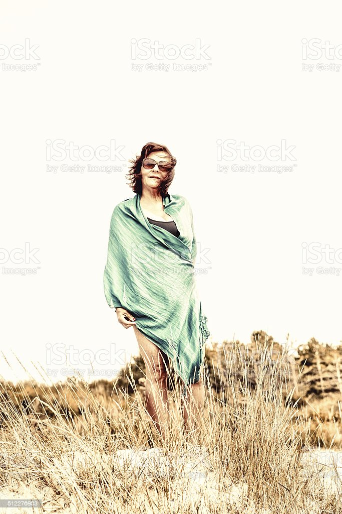 Mature hispanic woman standing in dunes stock photo