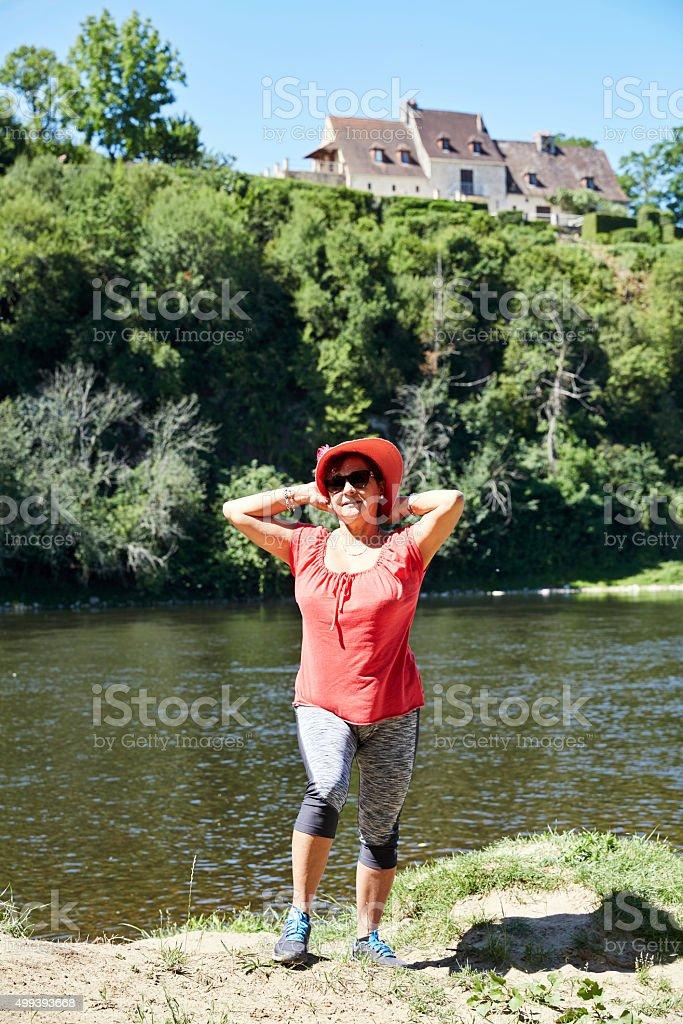 Mature hispanic woman standing on bank of River Dordogne stock photo