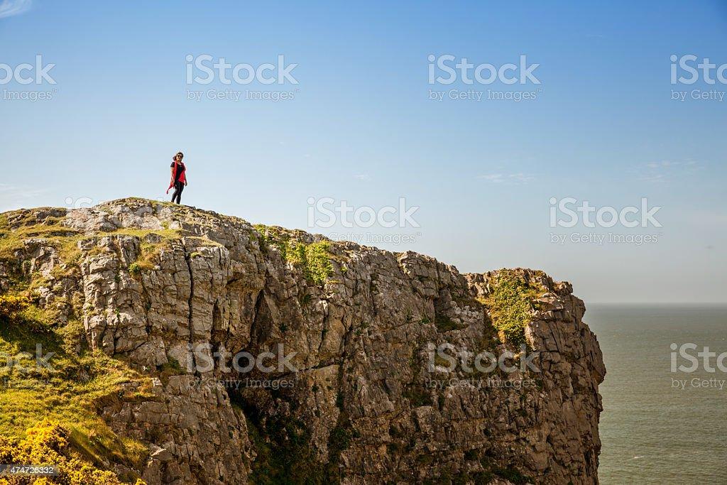 Mature hispanic woman standing on remote coastal headland stock photo