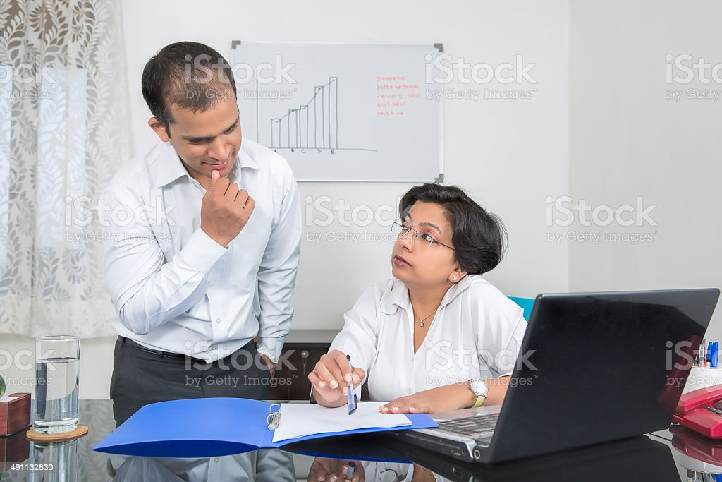 Mature Indian businesswoman giving Instructions to Subordinates at her office. stock photo