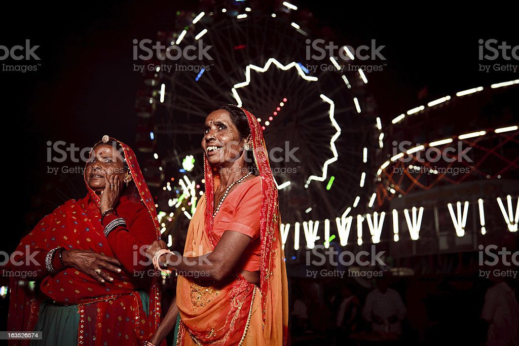 mature indian ladies in front of a ferris wheel royalty-free stock photo