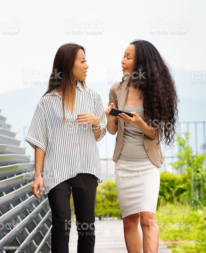 Mature Japanese business woman explains concept to her assistant stock photo