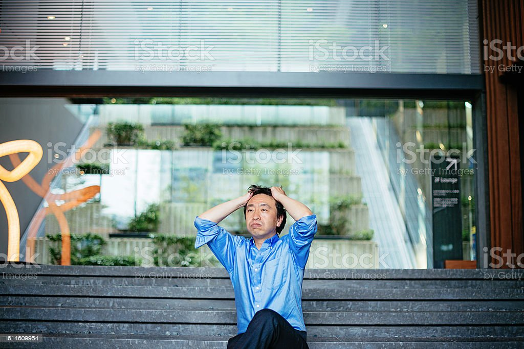 Mature Japanese businessman going mad after financial default stock photo