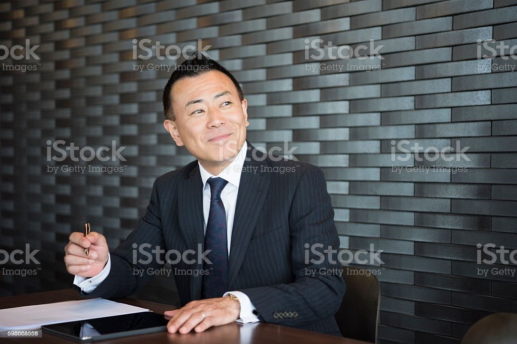 Mature Japanese businessman making notes, looking away stock photo