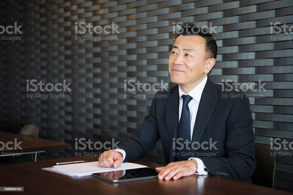 Mature Japanese businessman smiling at desk with paperwork stock photo
