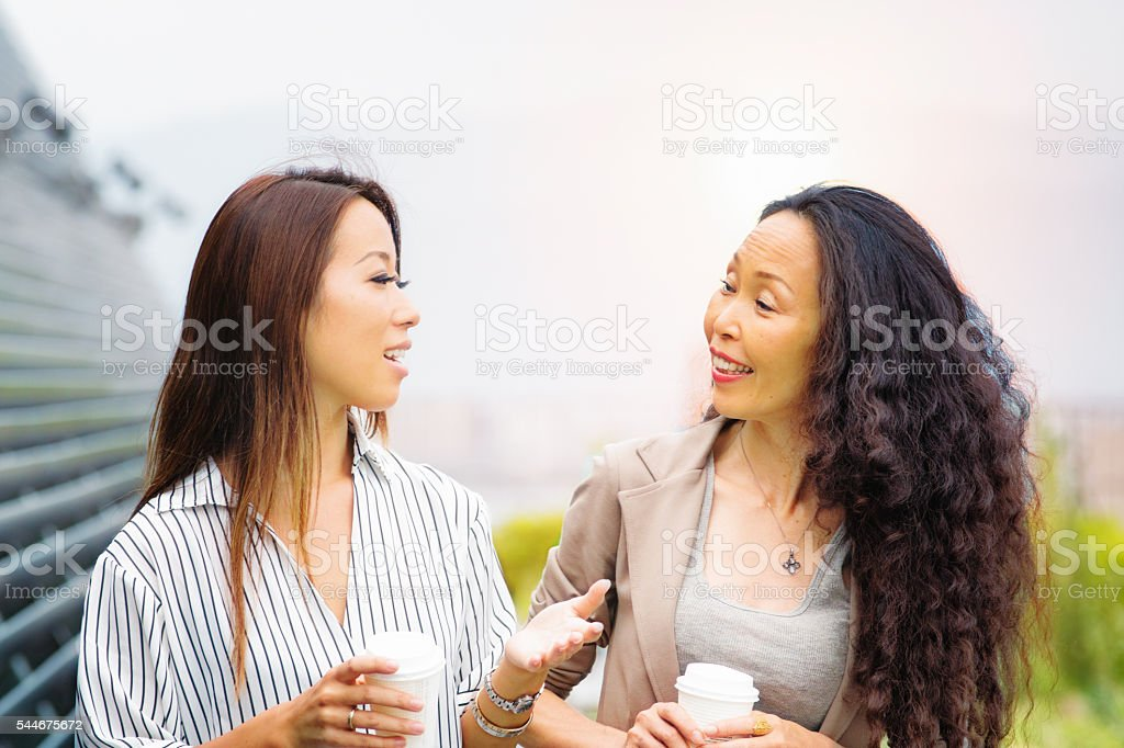 Mature Japanese businesswoman delighted to hear progress stock photo