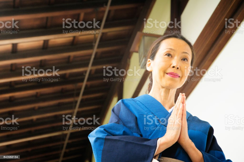 Mature Japanese Female walking in prayer at Buddhist Temple stock photo