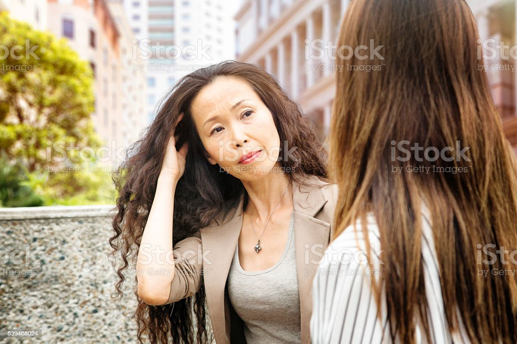 Mature Japanese woman concerned by conversation with younger woman stock photo