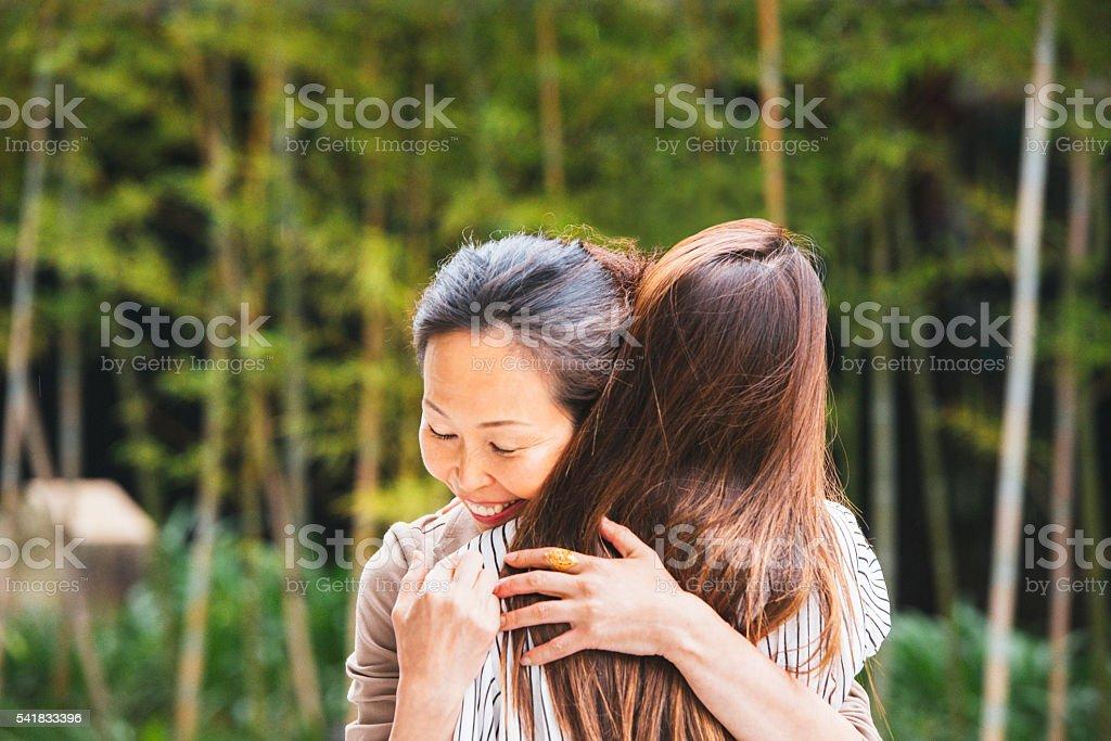 Mature Japanese Woman Hugs Daughter Outdoors in Kyoto Japan stock photo