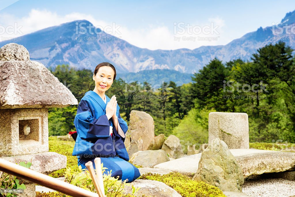 Mature Japanese woman praying portrait at country garden stock photo