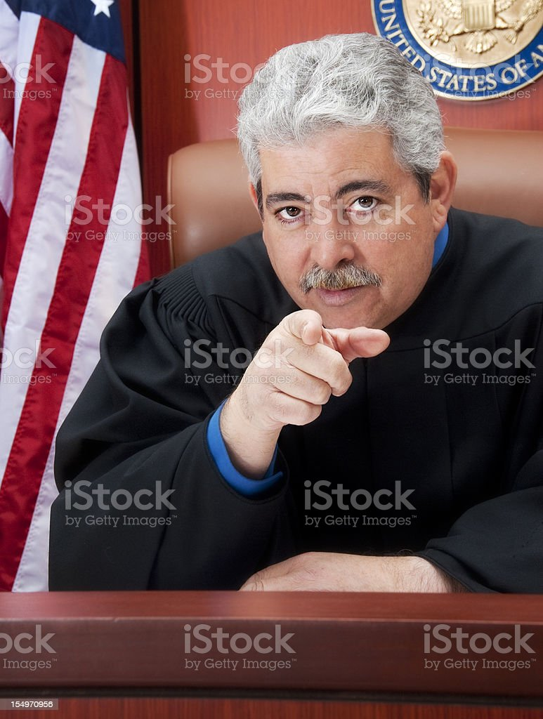 Mature judge at the bench with serious look pointing finger royalty-free stock photo
