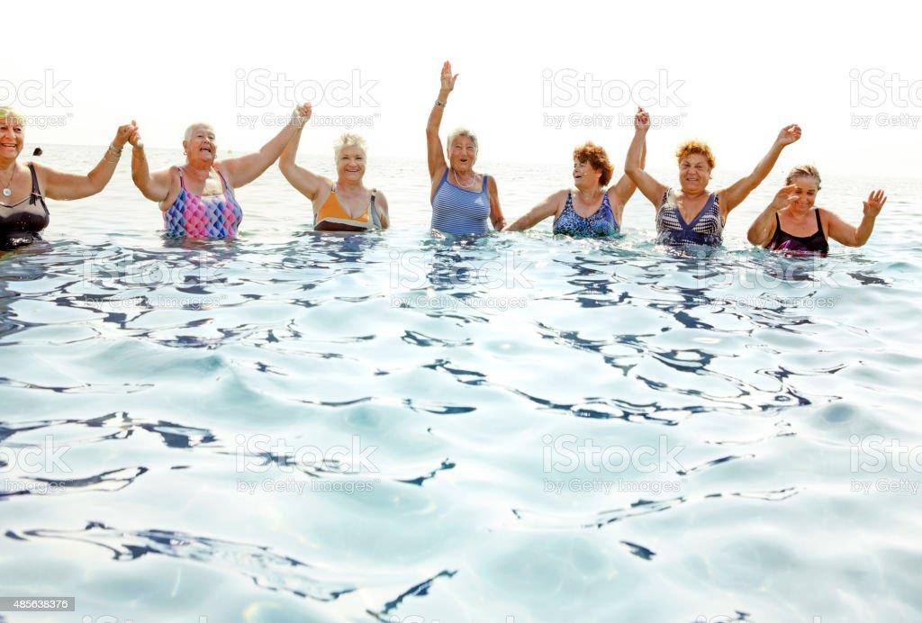 Mature ladies laughing on beach stock photo