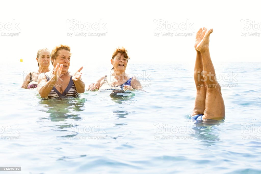 Mature ladies laughing on beach stock photo