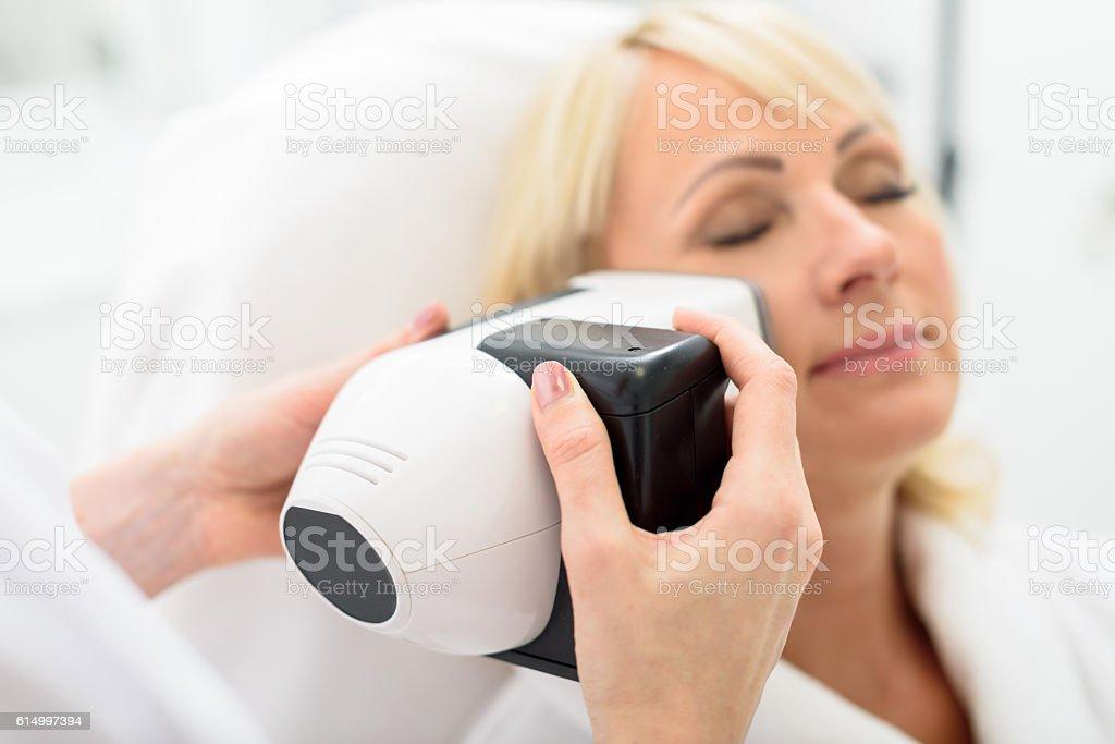 Mature lady enjoying skin rejuvenation by massager stock photo