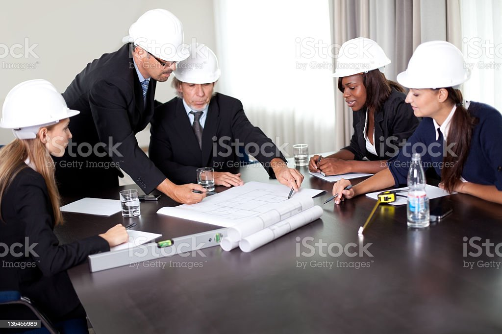 Mature male architect explaning his colleagues royalty-free stock photo