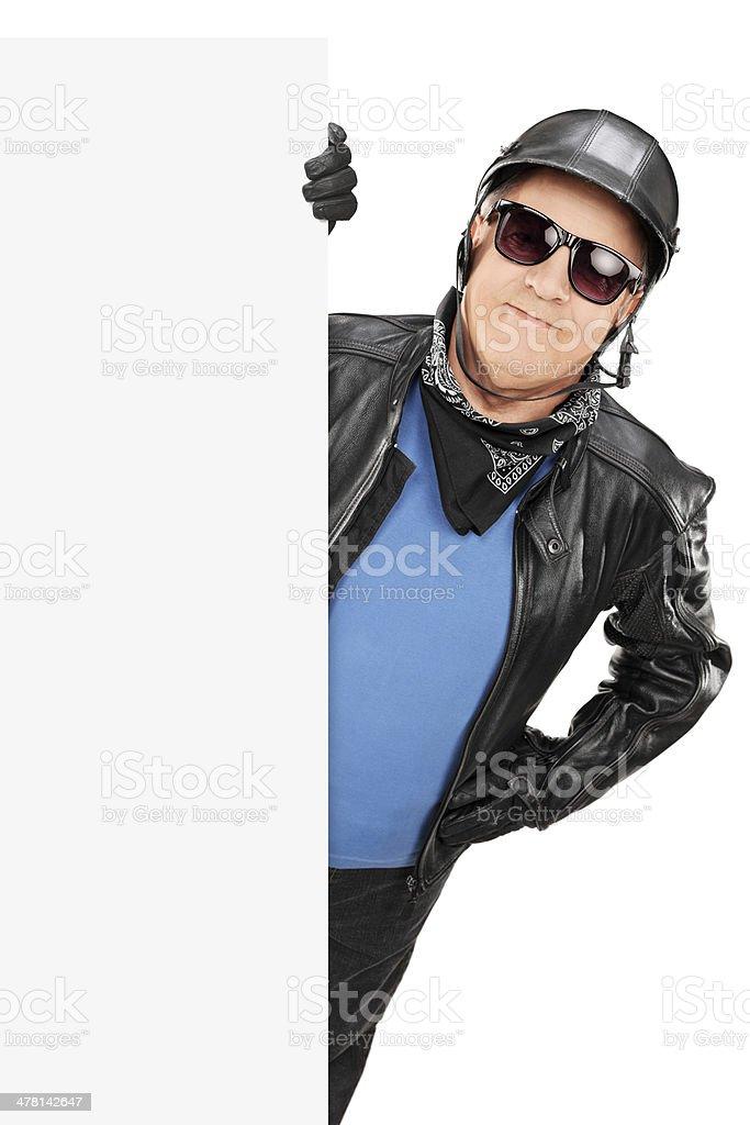 Mature male biker standing behind blank panel stock photo