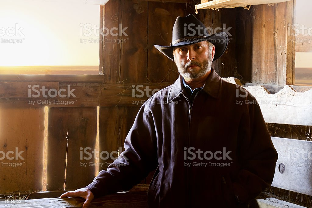 Mature Male Cowboy Portrait at Sunrise in Old Barn royalty-free stock photo